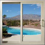 view of pool and backyard desert scene through patio door